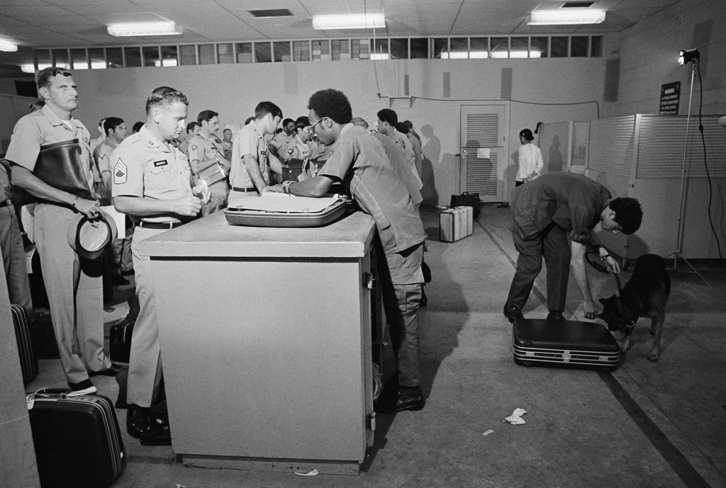 . Marijuana-sniffing dog, at right, checks over luggage of departing U.S. troops as they process through customs at Tan Son Nhut\'s Camp Alpha on Feb. 1, 1973.  Camp is the main processing center in South Vietnam for troop withdrawals.  All troops must be out of Vietnam by the end of March.  (AP Photo)