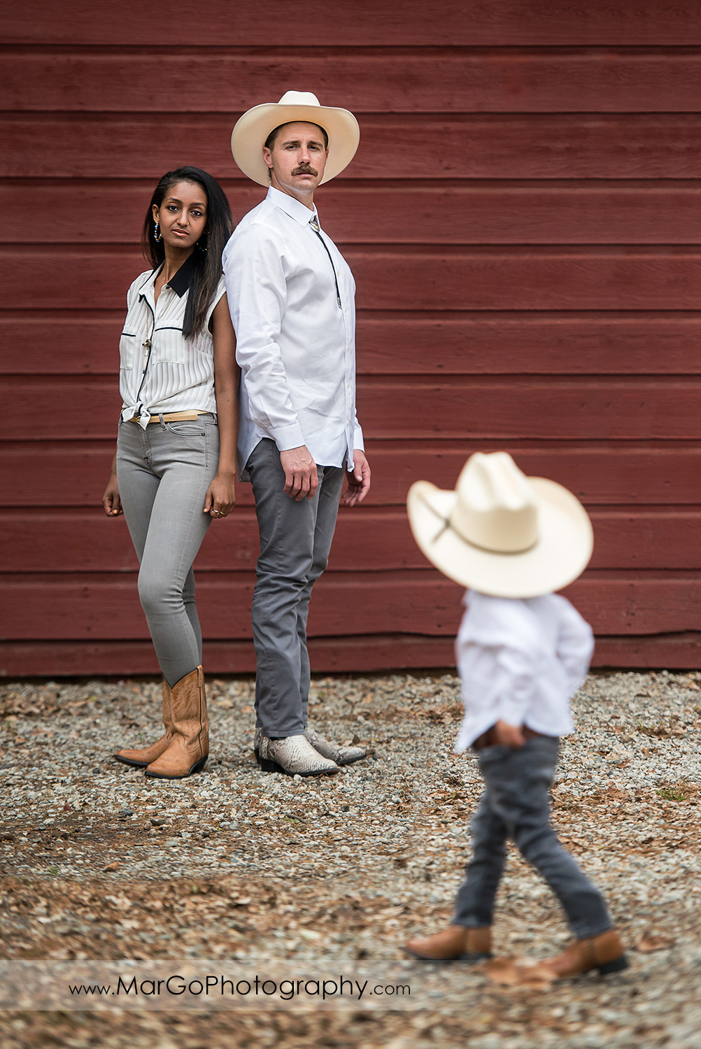 woman in white top and gray jeans and man in white shirt, gray jeans and cowboy hat standing back to back on the red wooden barn in Shinn Historical Park and Arboretum in Fremont