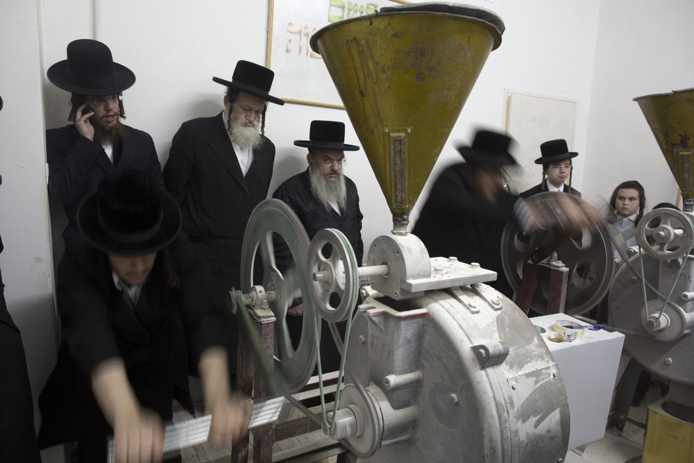 . Ultra-Orthodox Jewish men manually grind flour to be used for making of the Matzoth or unleavened bread on March 17, 2013, in Jerusalem. Religious Jews throughout the world eat matzoth during the eight-day Pesach holiday (Passover), which begins the March 25, with the sunset to commemorate the Israelis\' exodus from Egypt some 3,500 years ago and commemorate their ancestors\' plight by refraining from eating leavened food products. MENAHEM KAHANA/AFP/Getty Images