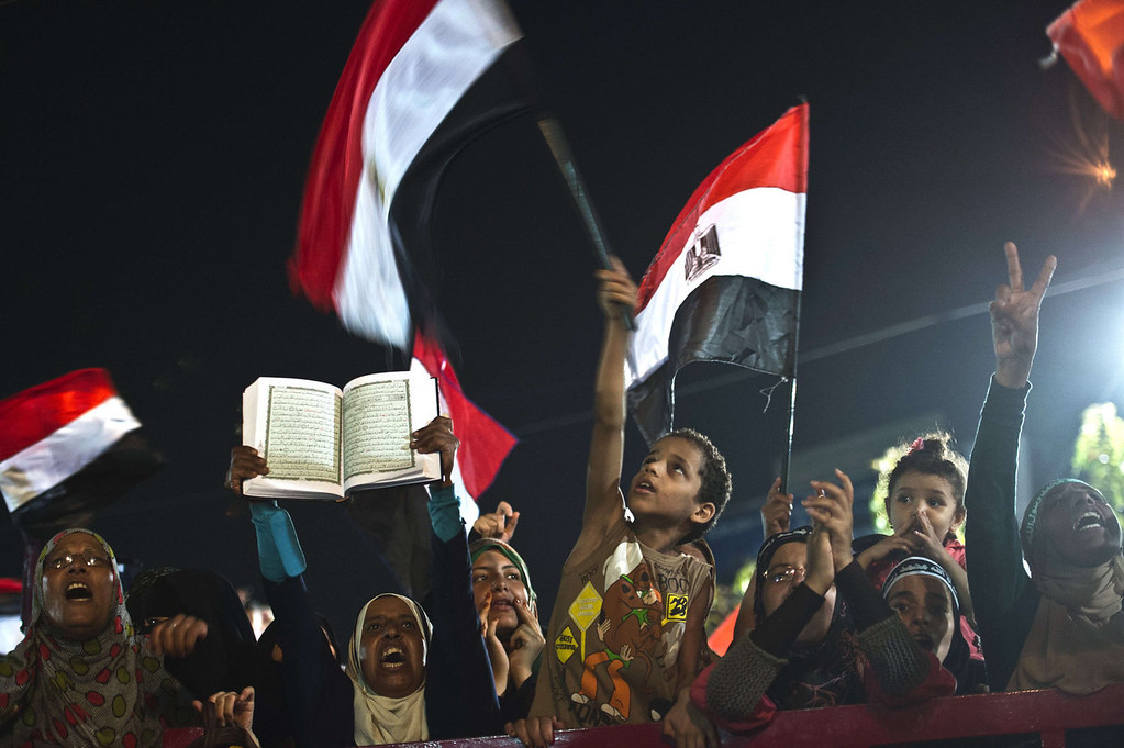 . A woman (2nd L) holds up a Kuran among members of the Muslim Brotherhood and supporters of Egypt\'s ousted president Mohammed Morsi during a sit-in protest outside the Rabaa al-Adawiya mosque in Cairo on August 12, 2013. Egypt\'s judiciary extended ousted president Mohamed Morsi\'s detention as his supporters marched through Cairo in defiance of the expiry of a government ultimatum to dismantle their huge protest camps.   KHALED DESOUKI/AFP/Getty Images