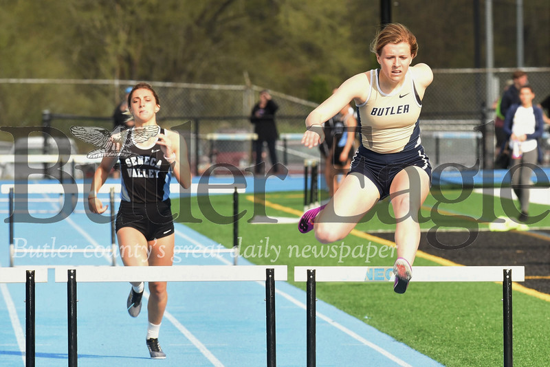 Butler's Anna Baxter clears a hurdle on her way to a win in the 300 meter hurdles. Lauren Chappelle  of Seneca(left) finished second. Seb Foltz/Butler Eagle