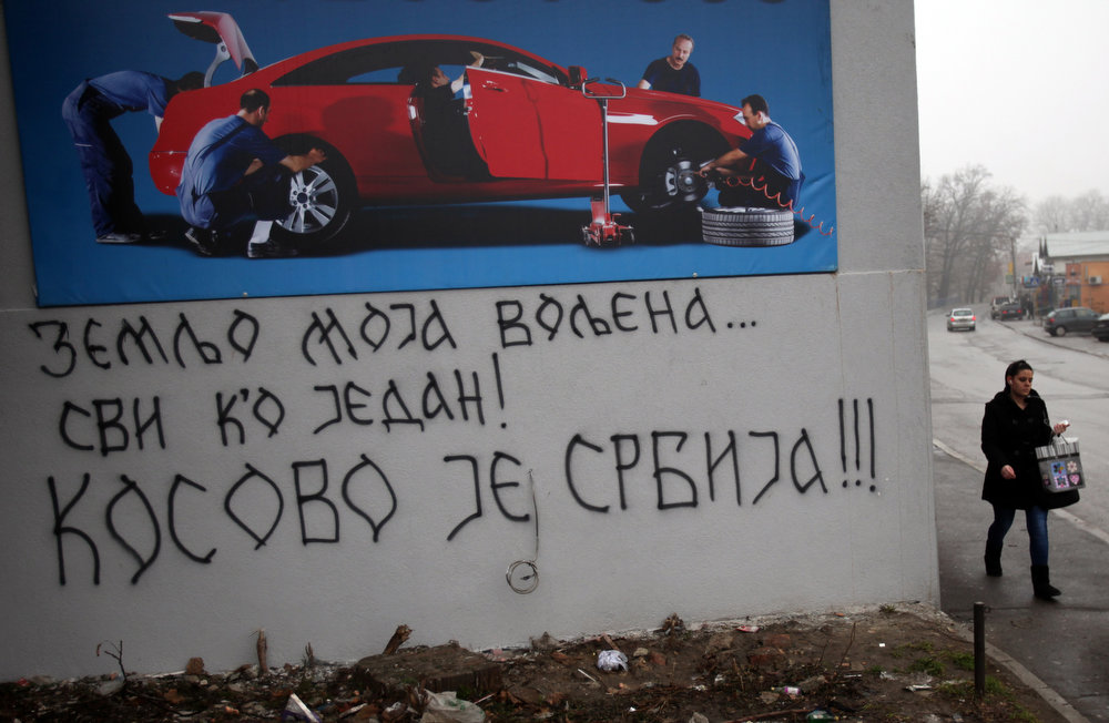 ". A woman walks past graffiti on a wall reading: ""My beloved country...\"", \""All as one!\"" and \""Kosovo is Serbia\"" in a suburb of  Belgrade, Serbia, Saturday, Feb. 16, 2013.  The predominantly ethnic Albanian leadership of Kosovo, Serbia\'s medieval heartland, proclaimed independence from Serbia on February 17, 2008 with Western backing. (AP Photo/Darko Vojinovic)"