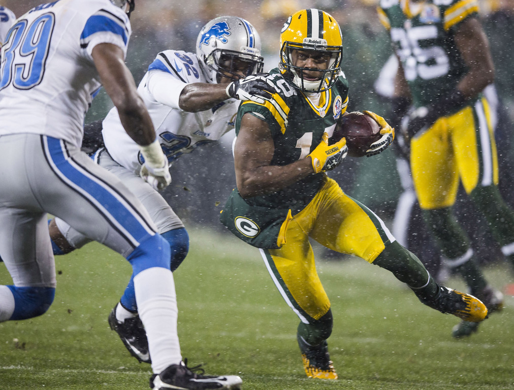 . GREEN BAY, WI - DECEMBER 9:  Randall Cobb #18 of the Green Bay Packers breaks through a tackle by Don Carey #32 of the Detroit Lions at Lambeau Field on December 9, 2012 in Green Bay, Wisconsin.  (Photo by Tom Lynn /Getty Images)