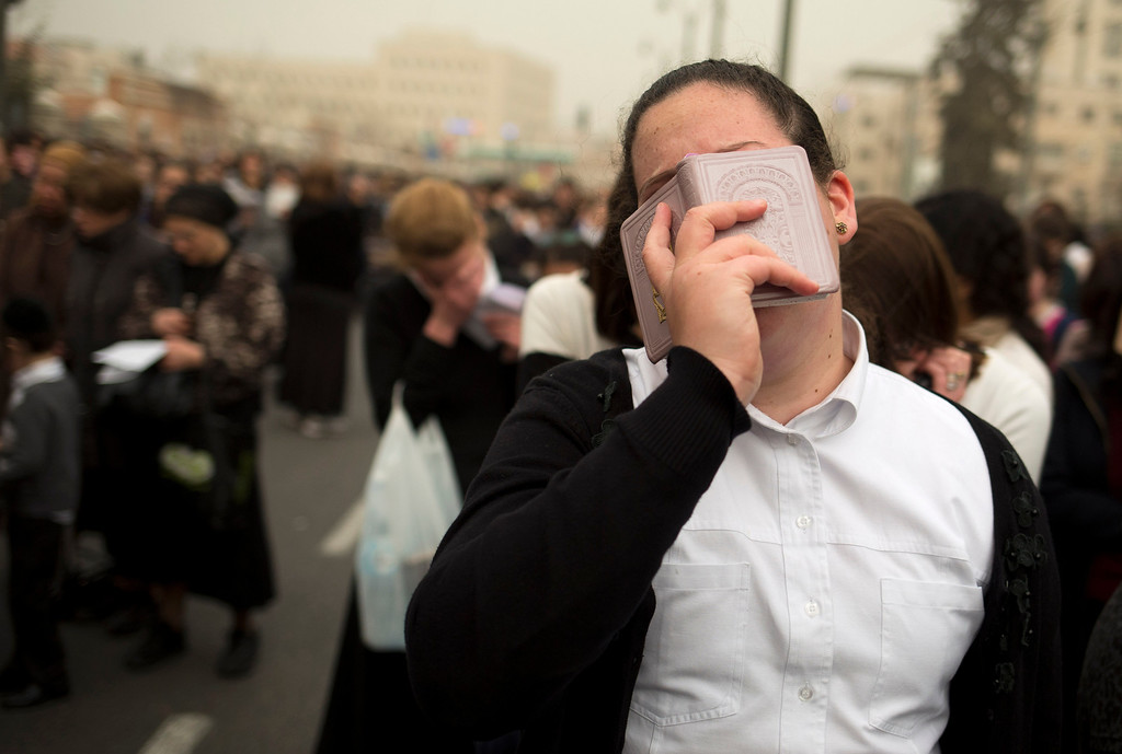 . An ultra-Orthodox woman prays during a mass protest in Jerusalem, Sunday, March 2, 2014. Hundreds of thousands of ultra-Orthodox Jews rallied in the streets of Jerusalem Sunday in a massive show of force against plans to force them to serve in the Israeli military. Usually only men attend such public demonstrations, but ultra-Orthodox community leaders encouraged women and young children to take part. (AP Photo/Dusan Vranic)