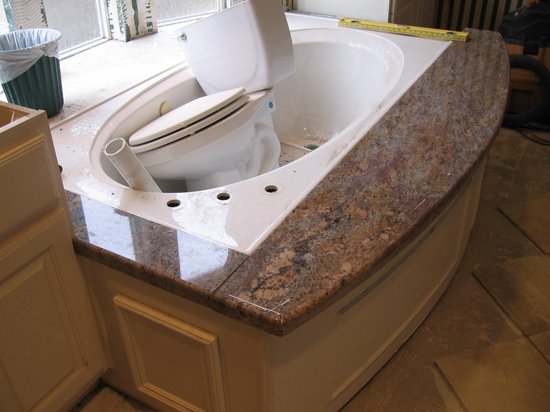 Installers are positioning the granite jacuzzi surround pieces.