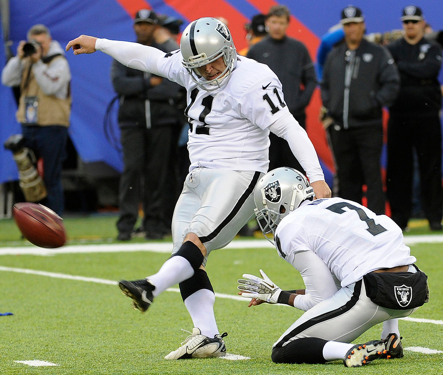 . Oakland Raiders kicker Sebastian Janikowski (11) boots a field goal with Marquette King (7) holding during the first half of an NFL football game against the New York Giants, Sunday, Nov. 10, 2013, in East Rutherford, N.J. (AP Photo/Bill Kostroun)