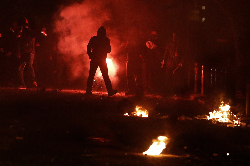 . Protesters throw stones at riot police during clashes in the Athens neighborhood of Exarchia, a haven for extreme leftists and anarchists, on Saturday, Dec. 6, 2014. (AP Photo/Petros Giannakouris)