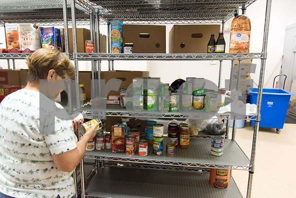 11/21/17 Wesley Bunnell | Staff The New Britain Salvation Army has seen a 100 percent increase in families looking for assistance from the food pantry since August in part due to the hurricanes. Food pantry volunteer Mirta Soto sorts through cans of food.