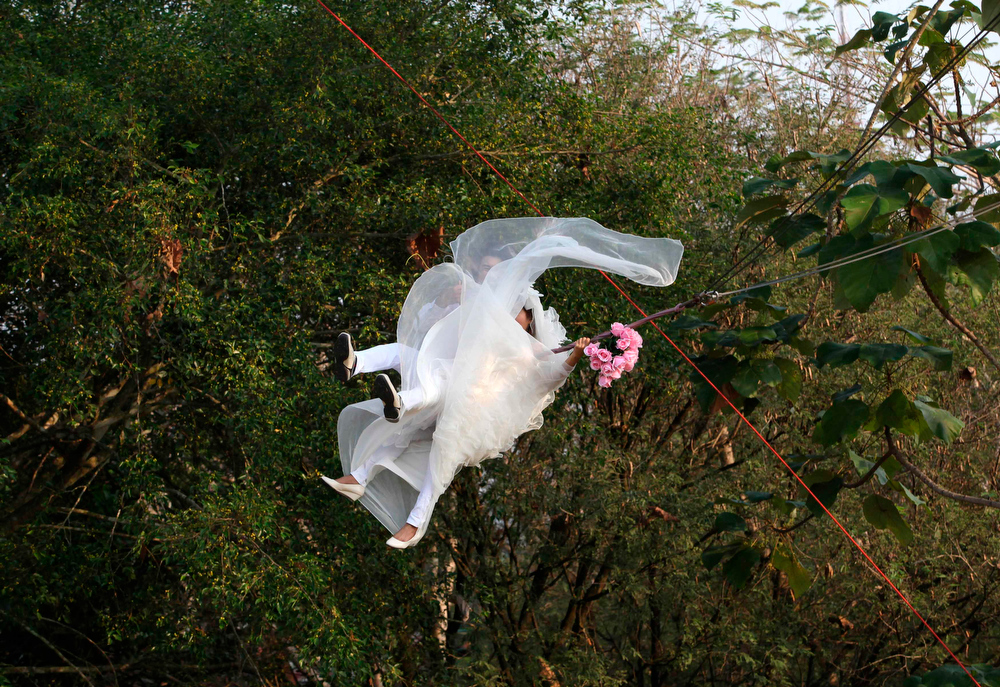 Description of . Thai groom Prasit Rangsiyawong (L), 29, and his bride Varuttaon Rangsiyawong, 27, fly while attached to cables during a wedding ceremony ahead of Valentine's Day in Prachin Buri province, east of Bangkok February 13, 2013. Three Thai couples took part in the wedding ceremony arranged by a Thai resort that aimed to strengthen the relationships of the couples by doing fun activities.  REUTERS/Kerek Wongsa