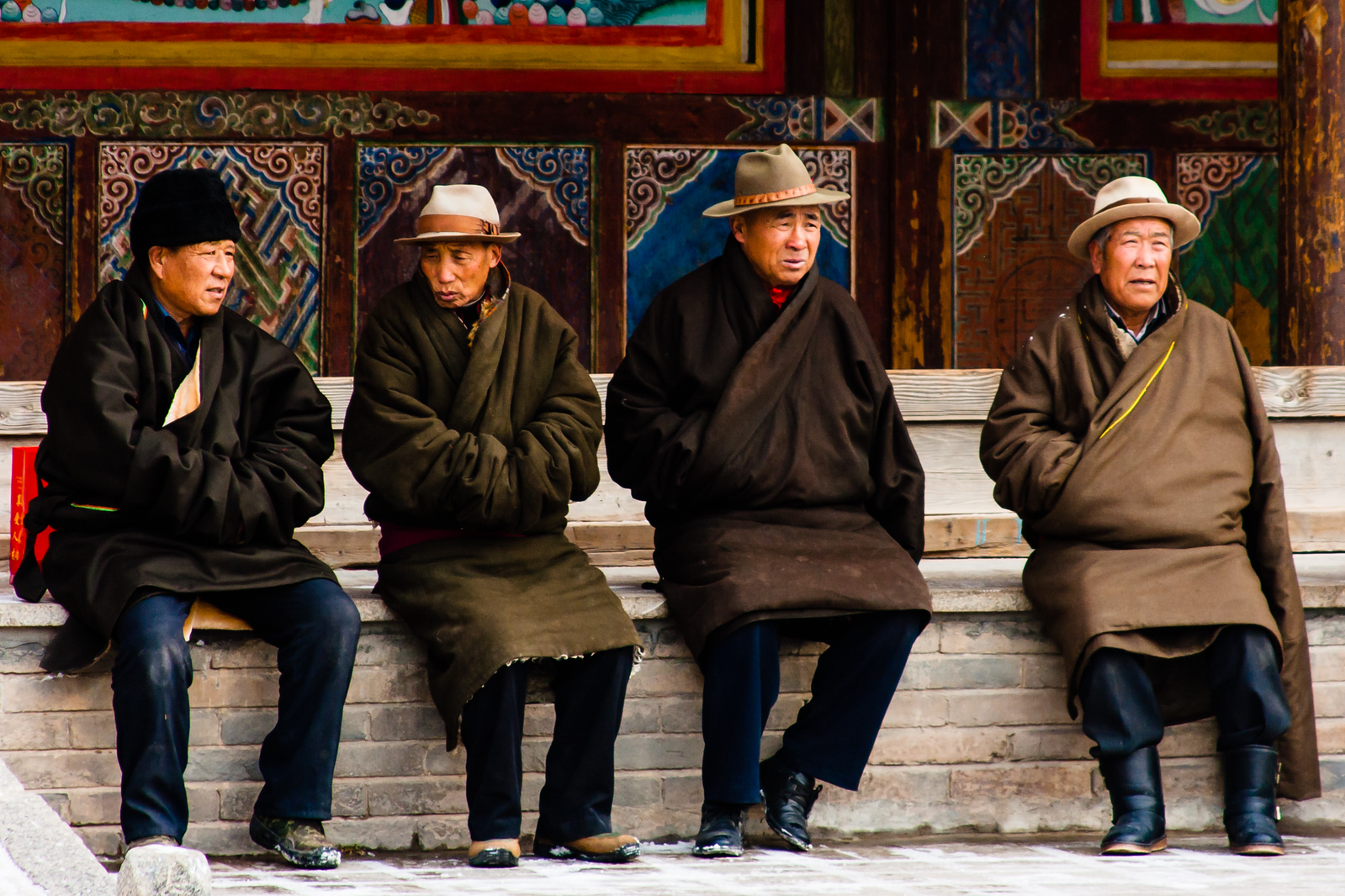 Elderly men dressed in traditional chubas wait patiently for the commencement of the Butter Tea Ceremony.