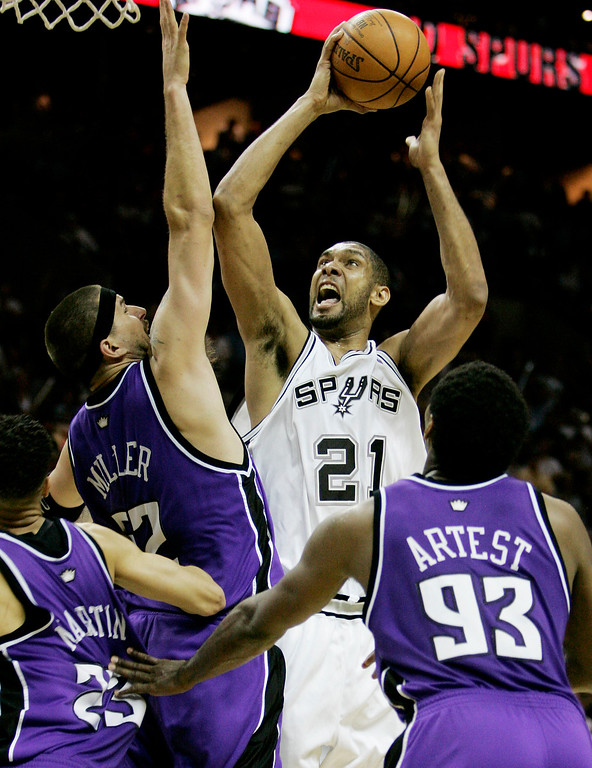 . FILE - In this May 2, 2006, file photo, San Antonio Spurs forward Tim Duncan (21) shoots over Sacramento Kings defenders Kevin Martin (23), Brad Miller (52) and Ron Artest (93) during the third quarter of their Western Conference NBA basketball playoff game in San Antonio. Duncan announced his retirement on Monday, July 11, 2016, after 19 seasons, five championships, two MVP awards and 15 All-Star appearances. It marks the end of an era for the Spurs and the NBA. (AP Photo/Eric Gay, File)