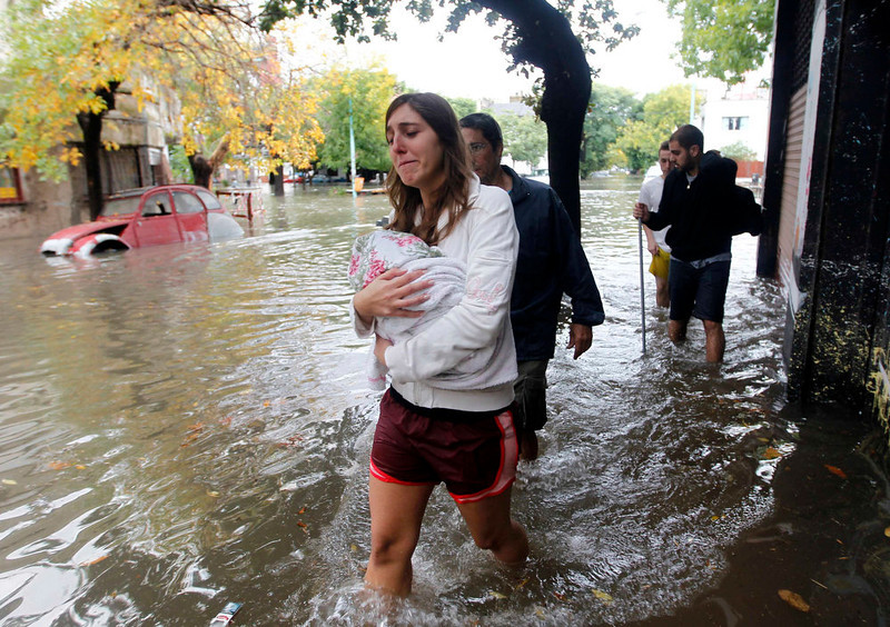 . People wade through a flooded street after a rainstorm in Buenos Aires April 2, 2013. Thunderstorms damaged property and vehicles, cut power and caused delays on flights in Buenos Aires and its suburbs. The City\'s SAME emergency service announced that the death toll has risen to five. REUTERS/Enrique Marcarian