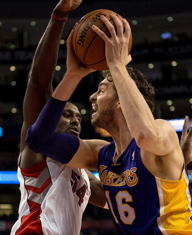 . Los Angeles Lakers center Pau Gasol (16) drives to the hoop past Toronto Raptors forward Patrick Patterson during first-half NBA basketball game action in Toronto, Sunday, Jan. 19, 2014. (AP Photo/The Canadian Press, Frank Gunn)