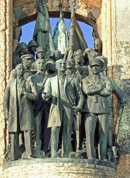 59-Atatürk and his comrades dressed in western-European clothing, symbolizing his roles as military commander-in-chief and as statesman. Mikhail Frunze, an important leader of the October Revolution, and Kliment Voroshilov, a Marshal of the Soviet Union, are among the group behind Atatürk. Their presence in the monument points to the military aid given by Lenin during the Turkish War of Independence.