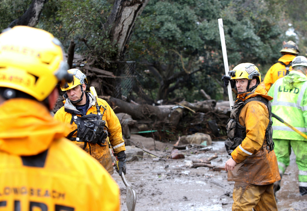 . Members of the Long Beach Search and Rescue team head into a debris-soaked area of Montecito, Calif. to look for survivors on Tuesday, Jan. 9, 2018. Several homes were swept away before dawn Tuesday when mud and debris roared into neighborhoods in Montecito from hillsides stripped of vegetation during a recent wildfire. (AP Photo/Daniel Dreifuss)