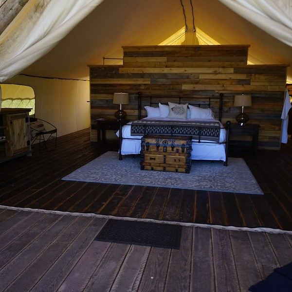 The interior of a tent with wooden wall and luxury bedding