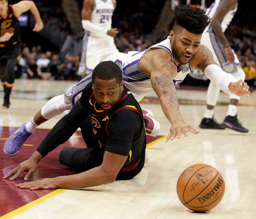 . Sacramento Kings\' Frank Mason III, right, and Cleveland Cavaliers\' Dwyane Wade battle for a loose ball in the first half of an NBA basketball game, Wednesday, Dec. 6, 2017, in Cleveland. (AP Photo/Tony Dejak)