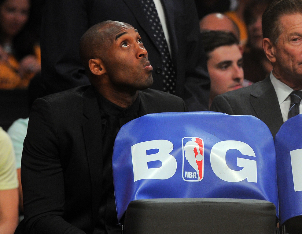 . Injured Lakers star Kobe Bryant checks the scoreboard from his seat behind the Lakers bench in the NBA season opener between the Lakers and Clippers at Staples Center in Los Angeles, CA on Tuesday, October 29, 2013.   (Photo by Scott Varley, Daily Breeze)