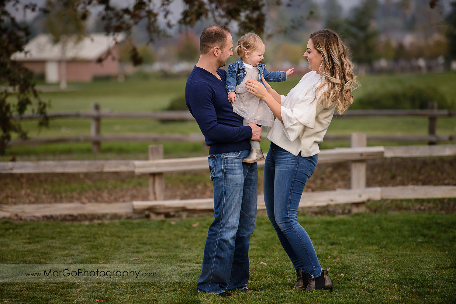 father wearing navy blue sweater and mother in white blouse holding little girl in white dress and jeans jacket standing on the grass during family session at San Jose Martial Cottle Park
