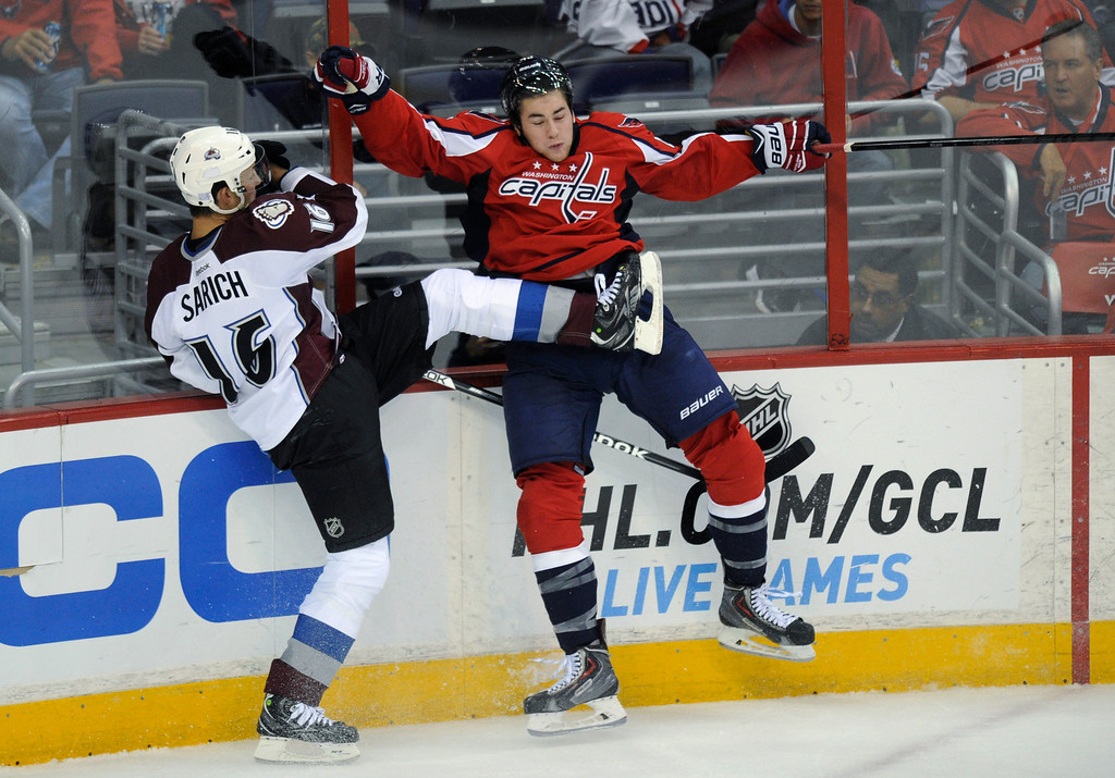 . Colorado Avalanche defenseman Cory Sarich (16) and Washington Capitals right wing Tom Wilson, right, collide against the boards during the third period an NHL hockey game, Saturday, Oct. 12, 2013, in Washington. The Avalanche won 5-1. (AP Photo/Nick Wass)