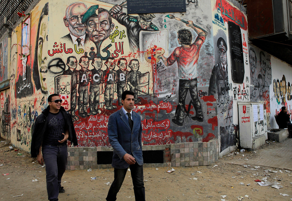 . Egyptian walk past revolutionary graffiti in Tahrir Square, Cairo, Egypt, Friday, Jan. 25, 2013. Egyptian opposition protesters are gathering in Cairo\'s Tahrir Square to mark the second anniversary of the uprising that toppled Hosni Mubarak\'s autocratic regime. (AP Photo/Thomas Hartwell)