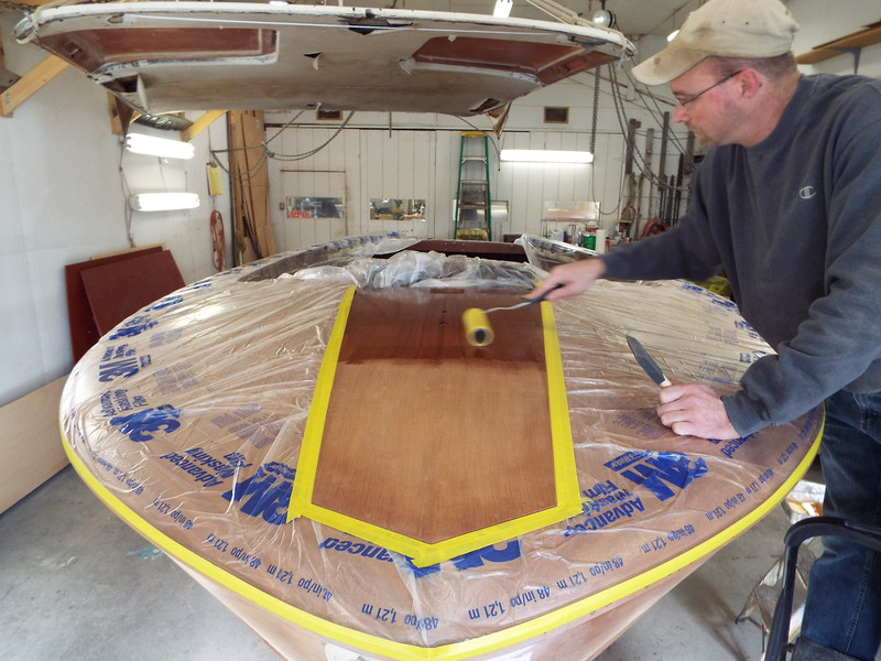 Applying the first of three coats of epoxy to the front king plank.
