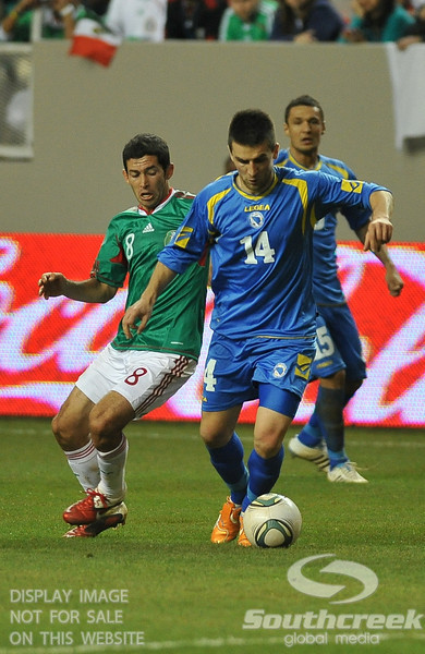 Mexico's Midfielder Israel Castro (#8) tries to take the ball away from Bosnia-Herzegovina's Forward Vedad Ibisevic (#14) in Soccer action between Bosnia-Herzegovina and Mexico.  Mexico defeated Bosnia-Herzegovina 2-0 in the game at the Georgia Dome in Atlanta, GA.