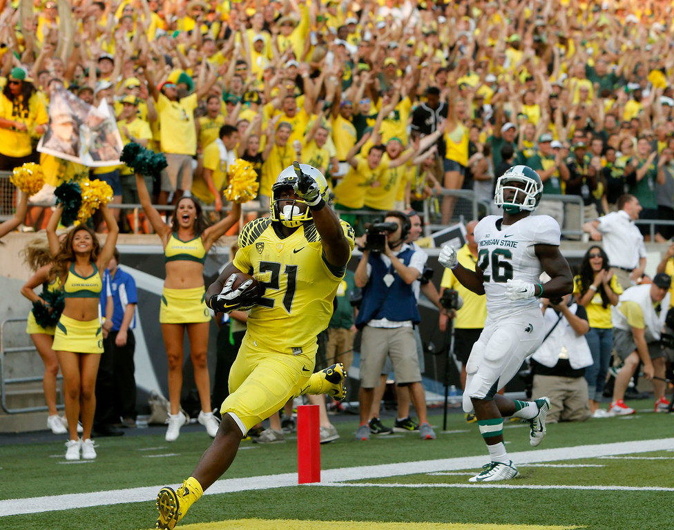 . Oregon\'s Royce Freeman, left, points to the fans after out running Michigan State\'s R. J. Williamson into the end zone in the 4th quarter of their college football game in Eugene, Oregon, Saturday Sept. 6, 2014. (AP Photo/Chris Pietsch)