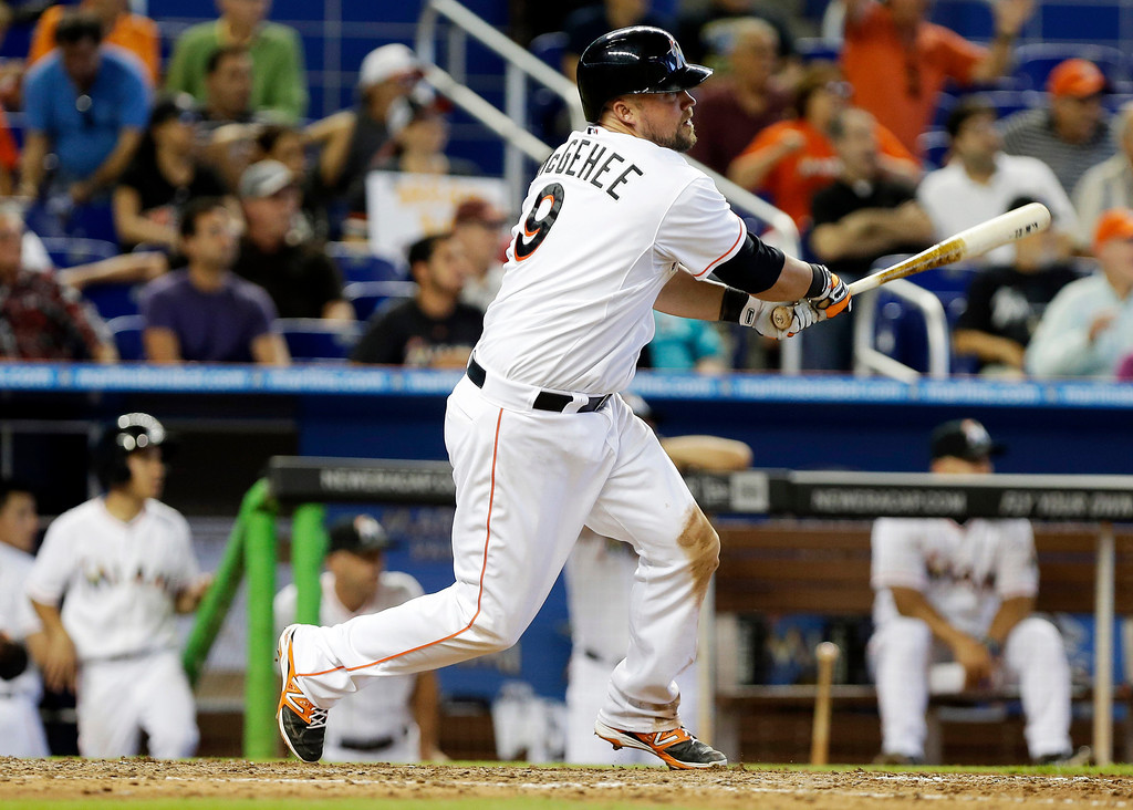 . Miami Marlins\' Casey McGehee hits a single to score Jeff Baker and Giancarlo Stanton in the eighth inning of a baseball game against the Colorado Rockies, Thursday, April 3, 2014, in Miami. The Marlins won 8-5. (AP Photo/Lynne Sladky)