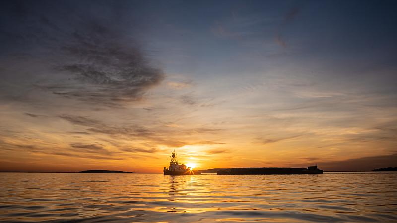 sun setting behind tugboat and barge.jpg