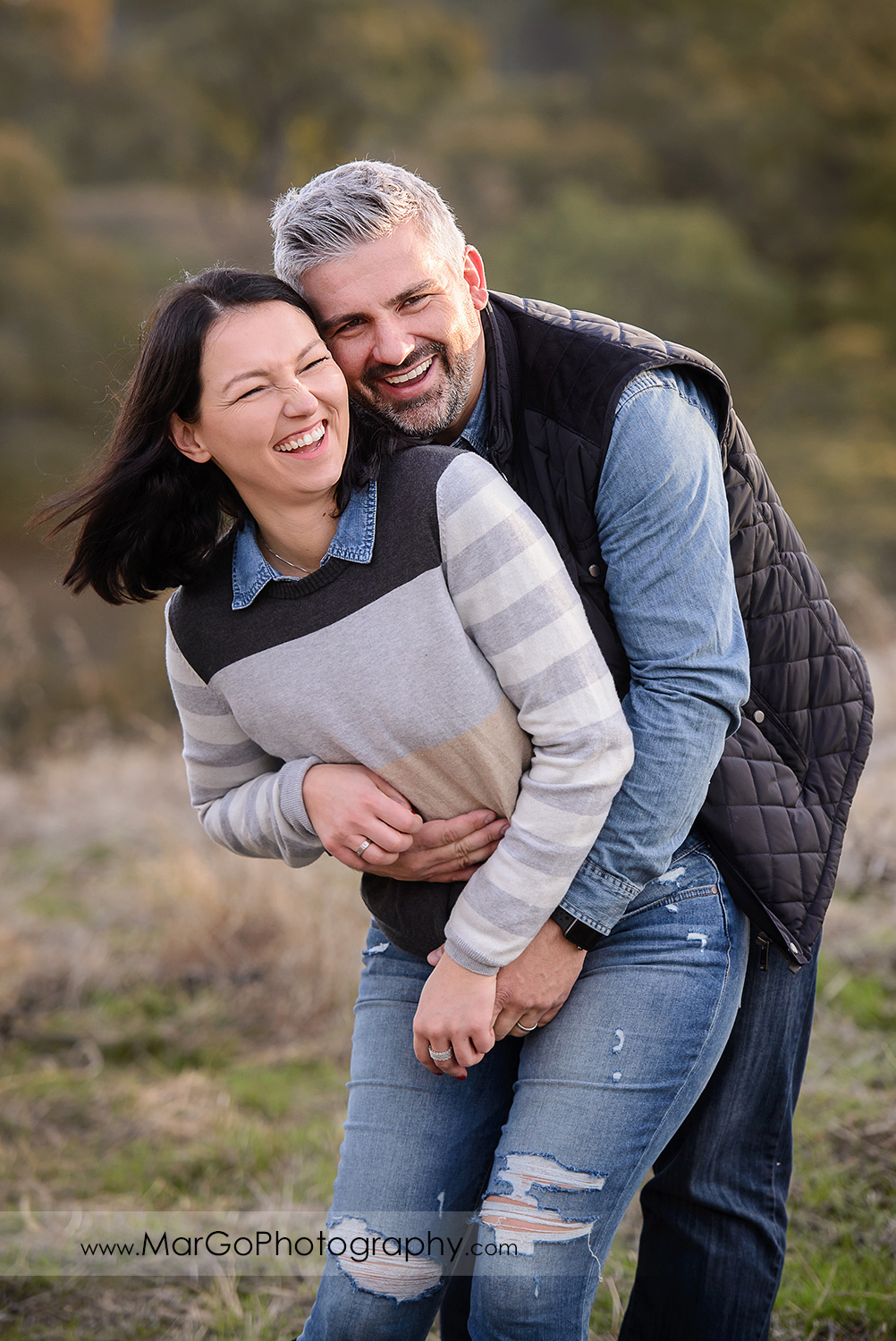 3/4 vertical portrait of man and woman wearing blue and grey clothes laughing during family session at Diablo Foothills Regional Park in Walnut Creek