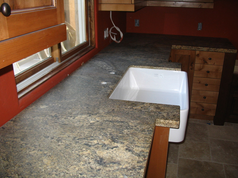 The kitchen sink, set in the granite countertop.