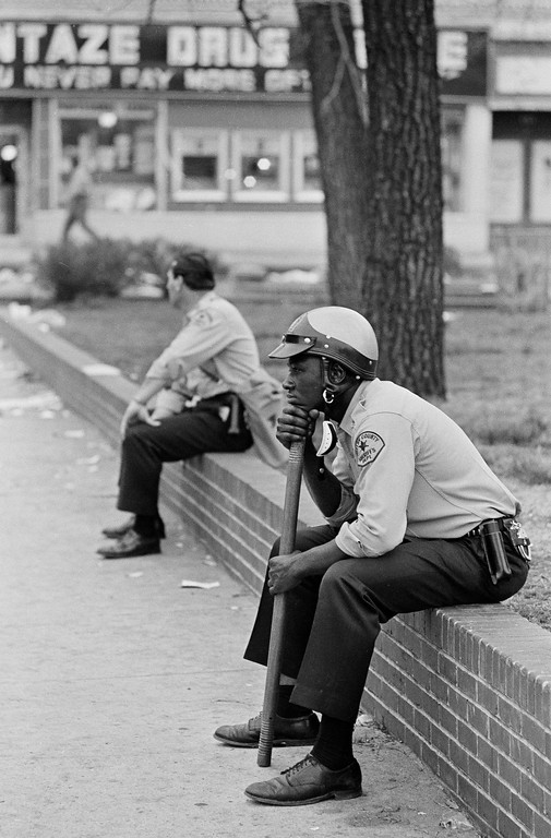 . Shelby County Deputy Sheriff Willie Wembley rests his chin on a riot stick as he and another deputy in the background rest on a brick wall that surrounds W.C. Handy Park in Memphis, Tenn., after rioting and looting broke out in the city, March 28, 1968. Policemen cleared the area after violence erupted midway through a march led by Dr. Martin Luther King Jr. in support of striking garbage workers. (AP Photo/Charles Kelly)