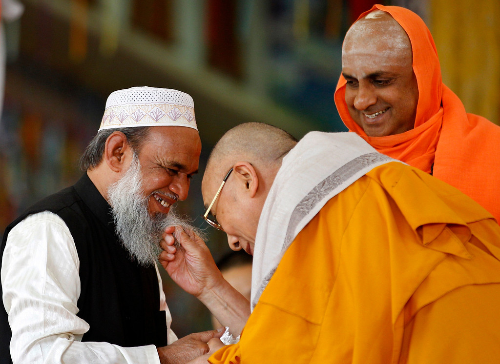. Hindu priest Shivratri Deshikendra, right, watches Tibetan spiritual leader the Dalai Lama, center, playfully tug the beard of a Muslim priest Mohammed Usman Shariff during an event organized to celebrate the Dalai Lama\'s 78th birthday at a Tibetan Buddhist monastery in Bylakuppe, about 220 kilometers (137 miles) southwest of Bangalore , India, Saturday, July 6, 2013. (AP Photo/Aijaz Rahi)