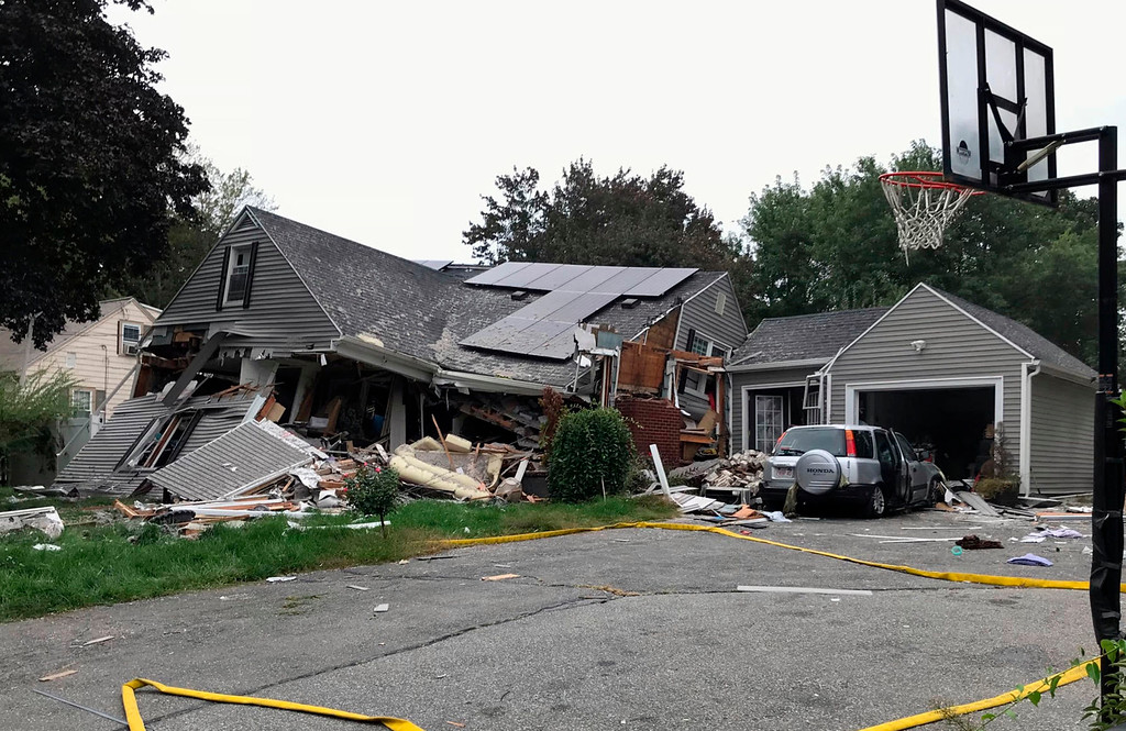 . ADDS IDENITY OF VICTIM LEONEL RONDON-  A collapsed home and car sit damaged on Chickering Street in Lawrence, Mass., Thursday, Sept. 13, 2018, after a series of gas explosions in several communities north of Boston. Authorities said Leonel Rondon died after the chimney toppled by the exploding house crashed into his car in the driveway. He was rushed to a Boston hospital but pronounced dead there in the evening. (Carl Russo/The Eagle-Tribune via AP)