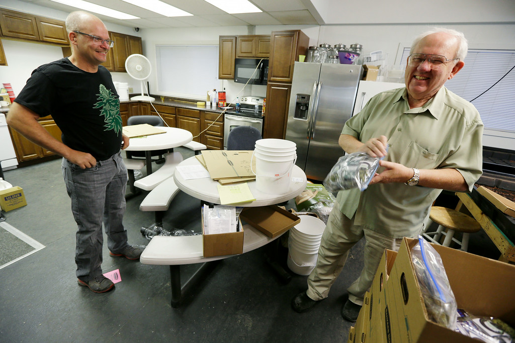 . Bob Leeds, owner of Sea of Green Farms, right, has a laugh with farm director Phil Tobias, as they load packets of recreational marijuana into boxes, Tuesday, July 8, 2014, in Seattle, for delivery to a store in Bellingham, Wash. It was the first delivery for the company since retail licenses were issued by the state on Monday. (AP Photo/Ted S. Warren)