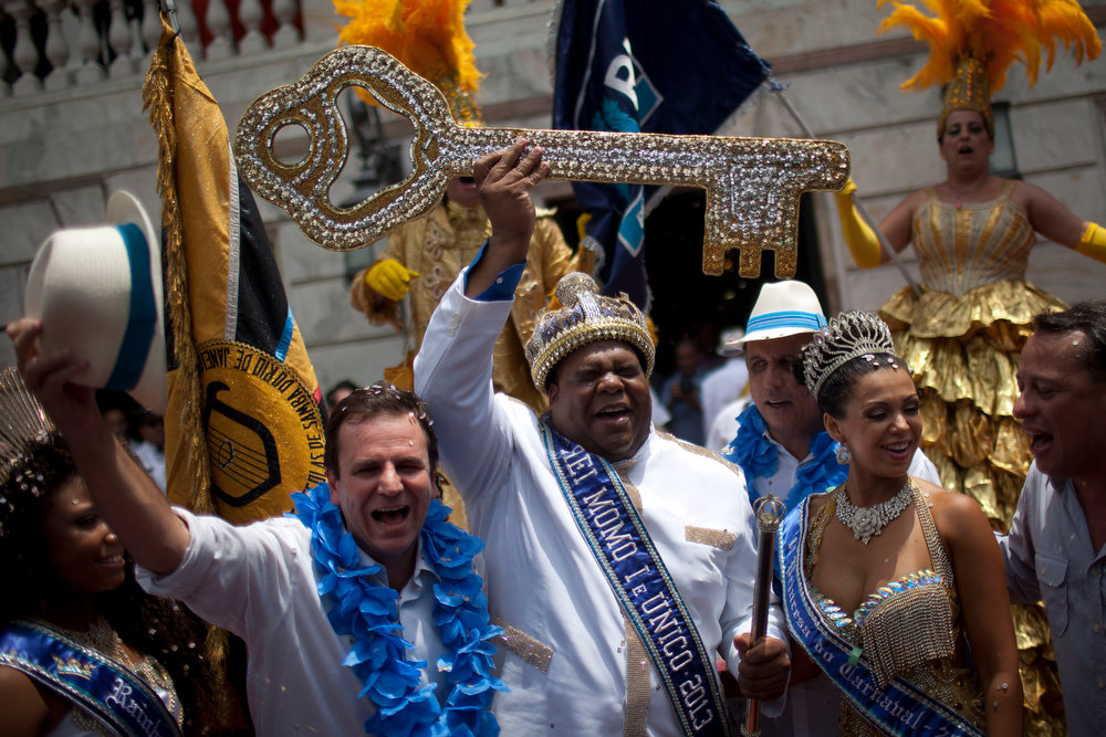 Description of . The mythical jester figure who reigns over Carnival, this year's King Momo; the crowned and costumed Milton Rodrigues Junior, center, holds up the key of the city that was given by Rio de Janeiro's Mayor Eduardo Paes, left, at the official ceremony kicking off the five-day bash, in Rio de Janeiro, Brazil, Friday, Feb. 8, 2013. (AP Photo/Felipe Dana)