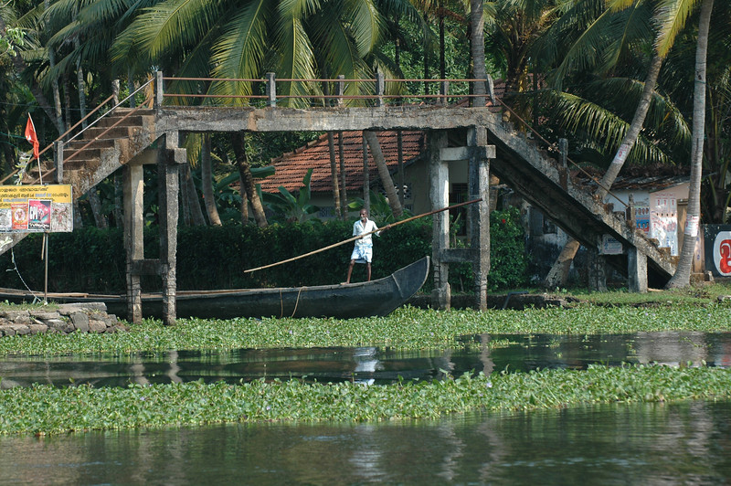 A boat moves under a walking bridge in the backwaters of Kerala