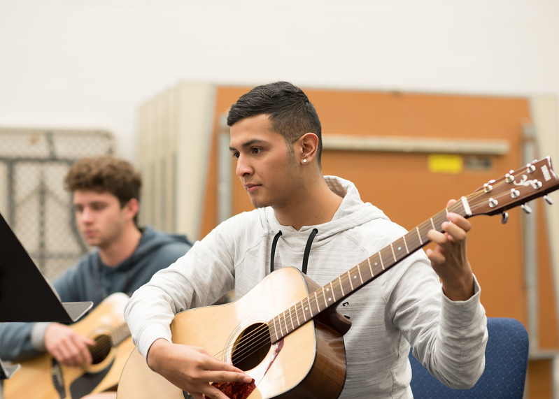 Student Thomas Lopez studies his music sheet as he learn to play Jingle Bells in Basic Guitar 1.