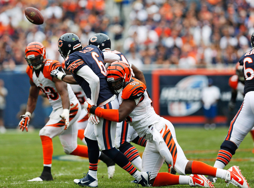 . Cincinnati Bengals defensive end Carlos Dunlap (96) tackles Chicago Bears quarterback Jay Cutler (6) as Cutler throws the ball during the second half of an NFL football game, Sunday, Sept. 8, 2013, in Chicago. (AP Photo/Charles Rex Arbogast)