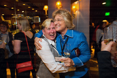 Elise Lindborg (left) of Zippy Dogs and Gladys Gillis of Starline Luxury Coaches hug when they see each other at the Puget Sound Business Journal's The Business Of Pride at the Paramount Theatre in Seattle on Thursday, May 26, 2016. (BUSINESS JOURNAL PHOTO | Dan DeLong)