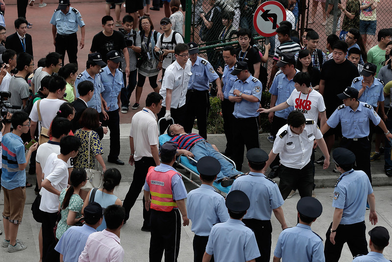 . An injured person is carried to an ambulance after a stampede during David Beckham\'s visit at Tongji University on June 20, 2013 in Shanghai, China.  (Photo by Lintao Zhang/Getty Images)