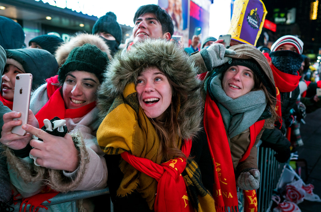 . Revelers gathered on Times Square in New York watch the ceremonial ball rise to the top of a pole high above the street Sunday, Dec. 31, 2017, in preparation for the ball drop during New Year\'s Eve celebrations. (AP Photo/Craig Ruttle)
