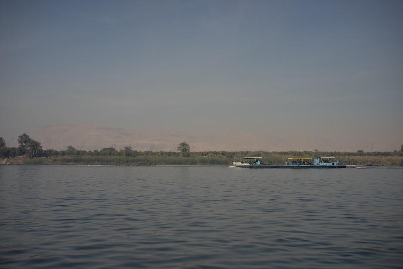 Lancha por el Nilo. Al fondo la montaña Tebana