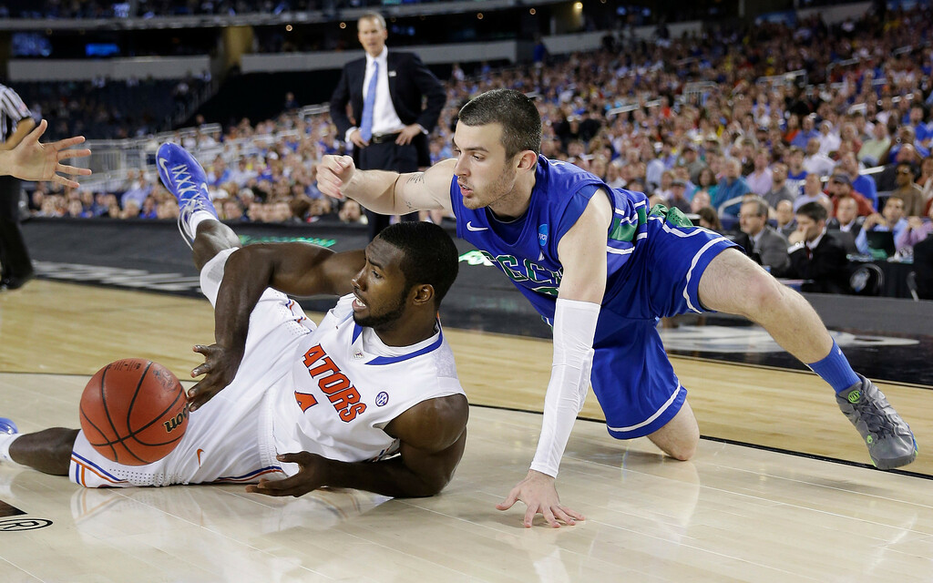 . Florida\'s Patric Young passes the ball away from Florida Gulf Coast\'s Brett Comer during the second half of a regional semifinal game in the NCAA college basketball tournament, Friday, March 29, 2013, in Arlington, Texas. (AP Photo/David J. Phillip)