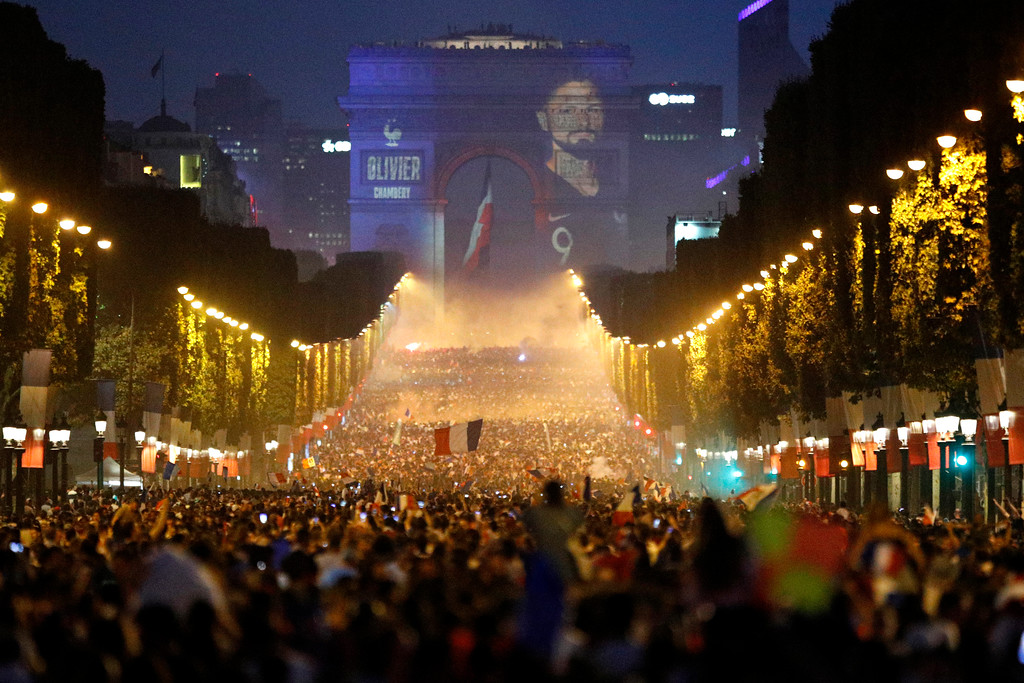 . The name of French soccer striker Olivier Giroud is projected onto the Arc de Triomphe as soccer fans invade the Champs Elysees avenue after France won the soccer World Cup final match between France and Croatia, Sunday, July 15, 2018 in Paris. France won its second World Cup title by beating Croatia 4-2 . (AP Photo/Francois Mori)