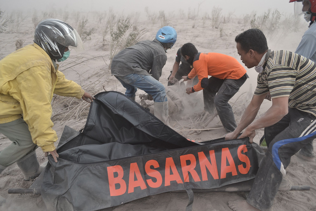 . Rescuers recover the body of a victim at a village in Karo district following eruptions of Mount Sinabung located in Indonesia\'s Sumatra island on February 1, 2014.  AFP PHOTO / SUTANTA  ADITYA/AFP/Getty Images