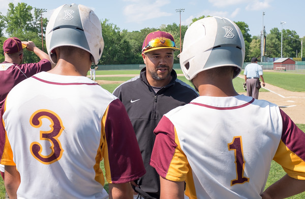 05/30/18 Wesley Bunnell | Staff New Britain baseball defeated Enfield 4-3 with a walk off bases loaded single in the bottom of the 7th in a first round CIAC Class LL tournament game. Head coach Roberto Mercado speaks to players Guillermo Burgos (3) and Danniel Rivera (1) before their at bats.