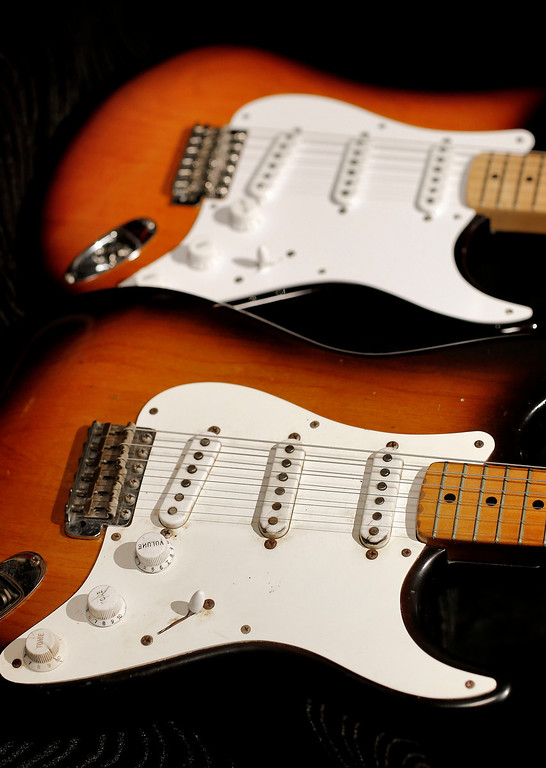 """. An original 1954 Fender Stratocaster, foreground, is shown next to a 2014 model at a studio in Scottsdale, Ariz. on Friday, Jan. 10, 2014. The Stratocaster has a unique voice that differs from other electric guitars due to its 3 pickups and has been described as \""""glassy,\"""" \""""bright\"""" or \""""clean.\"""" (AP Photo/Matt York)"""
