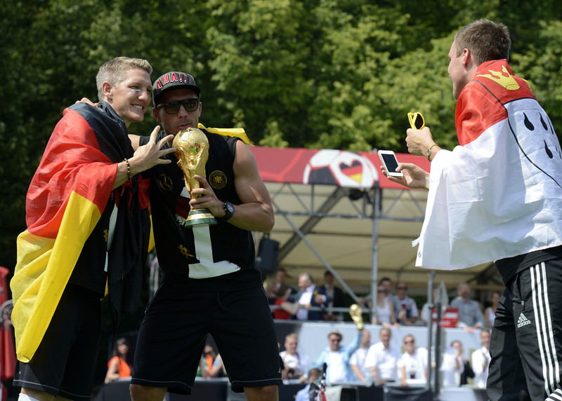 . Germany\'s national footbal team midfielder Bastian Schweinsteiger and midfielder Lukas Podolski (L-R) pose for a photo during celebrations of the German national team at Berlin\'s landmark Brandenburg Gate to celebrate their FIFA World Cup title on July 15, 2014. Germany won their fourth World Cup title, after 1-0 win over Argentina on July 13, 2014 in Rio de Janeiro in the FIFA World Cup Brazil final game. (CLEMENS BILAN/AFP/Getty Images)